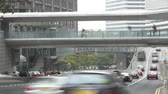 hong kong : Traffic speeds along road as commuters use pavement and walkway.