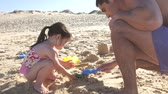 traje : Father helping daughter as she makes sandcastle.