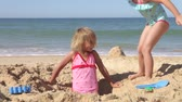 dámské plavky : Two young girls run around hole in the sand before one jumps in.