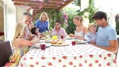 meal : Extended family group sitting down to meal as grandmother serves food. Stock Footage