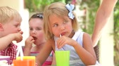 quatro : Children sitting at table eating party food and talking with friends.
