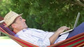 hat : Senior man rocking in hammock using laptop.