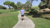 lifestyle shot : Senior man in park jogging towards and then past camera position.  Stock Footage