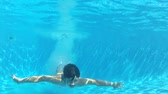 se divertindo : View from surface of pool as boy dives in before switching to underwater viewpoint where he swims towards camera and waves.  Stock Footage