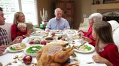 meal : Camera tracks across table as extended family sit and enjoy thanksgiving dinner.