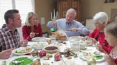 pečeně : Camera tracks across table as grandfather carves slices of turkey at thanksgiving dinner.