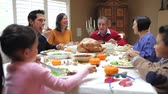 через : Camera tracks across table as extended family sit and enjoy thanksgiving dinner.