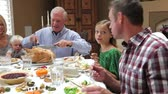 Camera tracks across table as grandfather carves slices of turkey at thanksgiving dinner.
