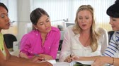 organization : Camera tracks across table as four women discuss document together. Stock Footage
