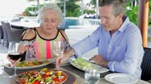 relaxed : Senior Couple Enjoying Meal In Outdoor Restaurant