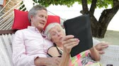 afetuoso : Senior Couple Relaxing In Beach Hammock Using Digital Tablet