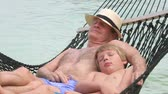 hat : Grandfather And Grandson Relaxing In Beach Hammock  Stock Footage