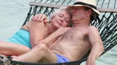hat : Senior Couple Relaxing In Beach Hammock