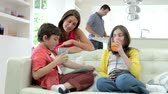 jogador : Children Playing With Digital Devices As Parents Make Meal Stock Footage