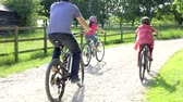 três pessoas : Father And Children On Cycle Ride In Countryside