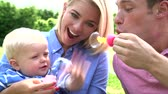 fangen : Eltern Blowing Bubbles For Young Boy im Garten