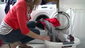 arruela : Woman Loading Clothes Into Washing Machine