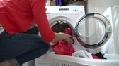 lavanderia : Woman Loading Clothes Into Washing Machine