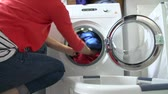 lavanderia : Slow Motion Of Woman Loading Clothes Into Washing Machine