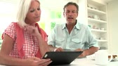 aborrecido : Middle Aged Couple Looking At Digital Tablet Having Argument Stock Footage