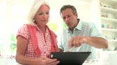 meal : Middle Aged Couple Looking At Digital Tablet Having Argument Stock Footage