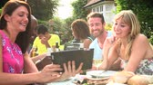 meal : Friends Having Barbeque At Home Looking At Digital Tablet