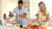 four people : Parents Preparing Family Breakfast In Kitchen