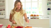 para cima : Woman Cutting Fresh Summer Fruit In Kitchen