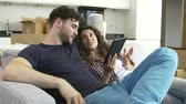 cardboard : Couple Relaxing On Sofa With Digital Tablet In New Home