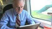 first class : Senior Businessman Commuting On Train Using Digital Tablet Stock Footage