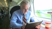 выстрел : Senior Businessman Commuting On Train Using Digital Tablet Стоковые видеозаписи