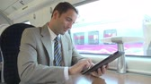 first class : Businessman Commuting On Train Using Digital Tablet Stock Footage