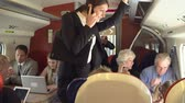 first class : Businesswoman Using Mobile Phone On Busy Commuter Train