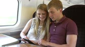 sáně : Young Couple Reading E Book On Train Journey