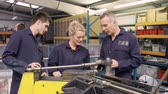 três pessoas : Engineer Teaching Apprentices To Use Tube Bending Machine