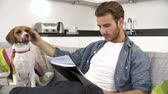 kavkazský ethnicity : Man Looking At Paperwork And Playing With Pet Dog At Home