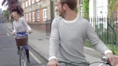 kavkazský ethnicity : Couple Cycling Along Urban Street Together