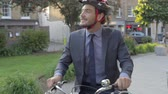 kavkazský ethnicity : Businessman Riding Bike Through City Park Dostupné videozáznamy