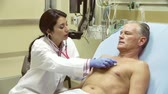 грудь : Doctor Examining Mature Male Patient In Hospital Bed