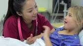 years : Young Girl Talking To Female Nurse In Intensive Care Unit