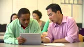 grade : Male High School Student With Teacher Using Digital Tablet Stock Footage