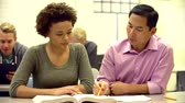 grade : Female High School Student With Teacher Discussing Textbook Stock Footage