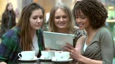 três : Group Of Young Female Friends With Digital Tablet In Café Stock Footage