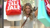 consumidor : Slow Motion Sequence Of Woman In Mall Holding Up Sale Bags