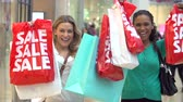 consumismo : Slow Motion Sequence Of Women In Mall Holding Up Sale Bags
