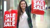 consumismo : Slow Motion Sequence Of Woman In Mall Holding Up Sale Bags