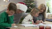 four people : Family Writing Christmas Cards Together At Home