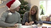quente : Couple Writing Christmas Cards Together Stock Footage