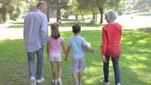 vnuk : Grandparents Walking With Grandchildren Through Park