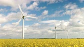 estupro : Time Lapse Sequence Of Wind Turbines In Field Of Rape Stock Footage